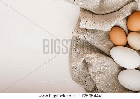Chicken eggs on the linen napkin on white table. view sverhu.mesto for text