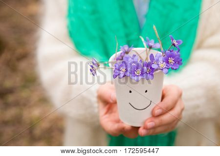 Woman holding beautiful snowdrops in a paper cup. first spring flowers in a forest. Wild flowers. spring concept.