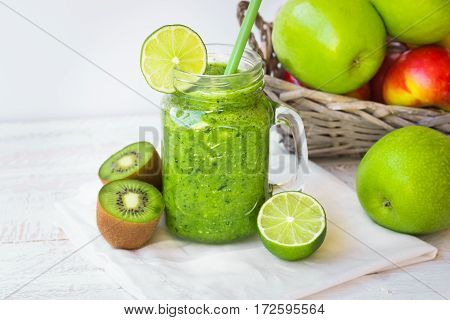 Green vegetable and fruit smoothie basket with apples kiwi lime on white wood table outdoors sunlight top angle view
