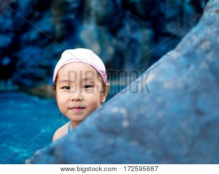 Asian girl is playing in the pool peekaboo action