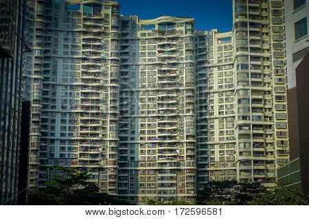 SHENZEN, CHINA - 29 JANUARY, 2017: Inner city streets and sorroundings of Nan Shan neighborhood, typical large apartment building, totally blue skies.