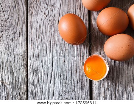 Fresh chicken eggs background. Brown and white eggs with cracked eggshell and yellow yolk on rustic wood table. Top view with copy space. Rural still life, natural healthy food concept.