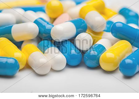 pile of medical pills and blue pills on a background