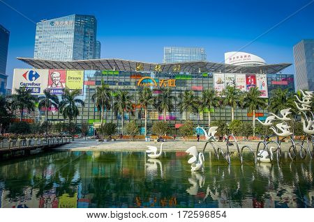 SHENZEN, CHINA - 29 JANUARY, 2017: Inner city streets and sorroundings of Nan Shan neighborhood, modern glass building with water lagoon in front, totally blue skies.