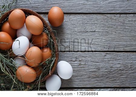 Poultry farm concept. Basket with fresh brown and white eggs on burlap textile at rustic wood background with copy space. Top view on sacking. Rural still life, natural organic healthy food.