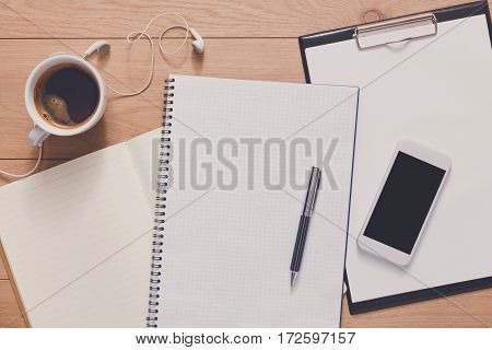 Writing, planning or preparing to exam background. Study and work in office mockup. Top view of spiral notebook, pen, coffee and mobile phone on wood