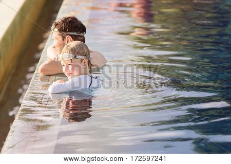 family of two father and son enjoying together at infinity pool at resort