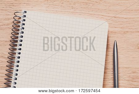 Spiral notepad and personal diary or organizer closeup, writing to do list concept. Office or student's stationery on wood. Working table top view. Education background with copy space on paper