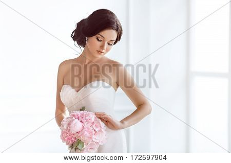 Beautiful bride perfect style. Wedding hairstyle make-up luxury wedding dress and bride's bouquet. Young attractive multi-racial Asian Caucasian model like a bride against white room at studio looking at bouquet.