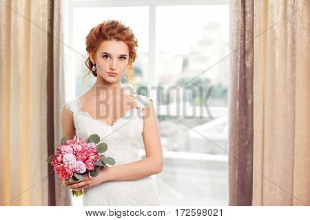 Wedding. Beautiful bride indoors with bouquet of flowers