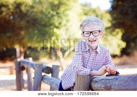 cute school boy student in glasses enjoying time outdoor back to school concept