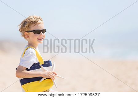 cheerful smiling boy in sunglasses holding beach bag and starfish at the beach with copyspace on the right side vacation concept