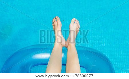 Young Woman Lying And Sunbathing In The Swimming Pool