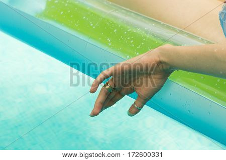 Young Woman Floating Her Hand In The Swimming Pool