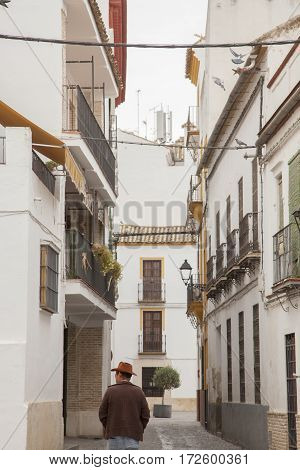 spanish man walking through a typical spanish street.