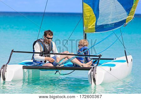 family of two father and son enjoying sailing together at hobie cat catamaran active healthy lifestyle