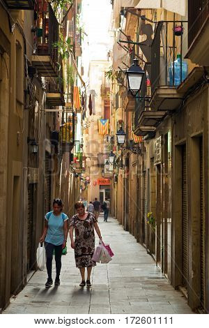 BARCELONA/ SPAIN - SEPTEMBER 29. Women with shopping bags walking on a narrow street in old district La Ribera on September 29, 2014 in Barcelona, Spain.