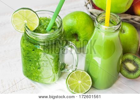 Jar mug with green vegetable smoothie and fruit juice in bottle with straw, apples, lime, kiwi on kitchen table outdoors, sunlight fleck