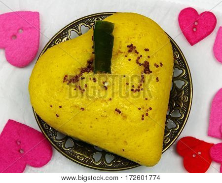A plate of heart shaped lentil dhokla an Indian snack with mustard seeds tempering