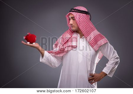 Arab businessman with piggybank  on gray background
