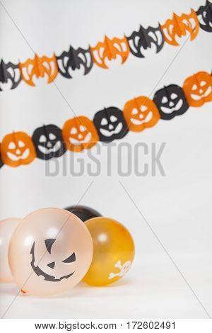 Halloween decoration with sacary balloons and pumpkins and paper bats isolated on white background