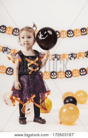 cute little child dresses with a witch costume isolated on Halloween background