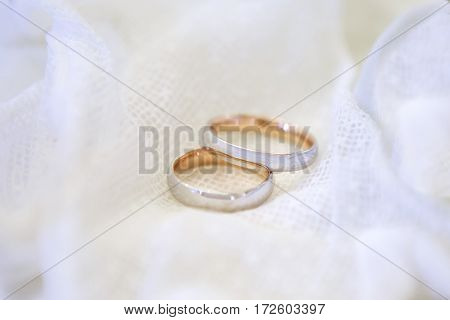 Two Golden wedding rings framed by white lace. A symbol of fidelity and marriage on a white background.