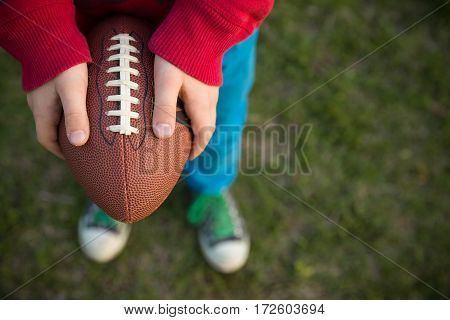 Top view on hands of little kid boy holding football on the stadium on a sunny day. Child ready to throw a football. Sport concept. Sport activities for children outdoors.