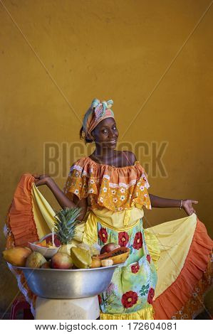 CARTAGENA DE INDIAS, COLOMBIA - JANUARY 24, 2017: Woman in traditional costume posing for a photograph whilst selling fresh fruit in the historic walled city of Cartagena de Indias in Colombia
