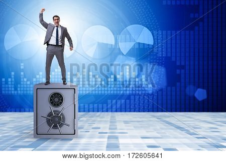 Excited businessman standing on top of safe