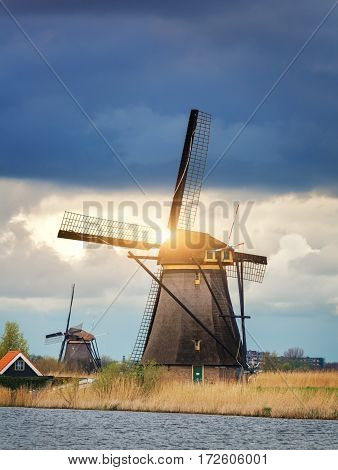 Windmills Against Cloudy Sky At Sunset In Kinderdijk, Netherlands