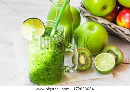 Jar mug with fresh green vegetable smoothie bottle with fruit juice with straw apples in basket lime kiwi wood table outdoors bright sun fleck top view