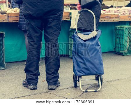 Person with wheeled shopping bag. Shopping at local outdoor market.