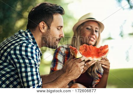 Friends enjoying nature and eating watermelon.Spring time.