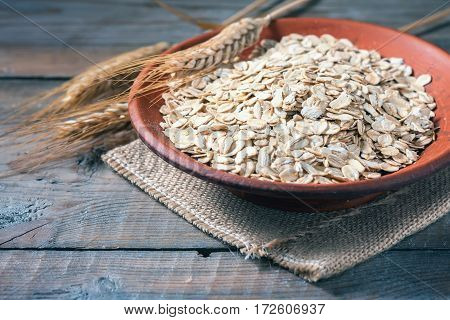 Oat Flakes On Wooden Table. Healthy Food Concept.