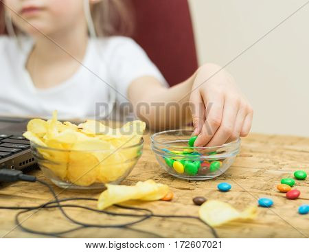Girl eating candy and potato chips of the laptop. Unhealthy eating child at the computer.