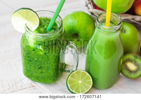 Glass mug with fresh green vegetable smoothie bottle with fruit juice apples kiwi lime on wood table outdoors sunliht flecks close up