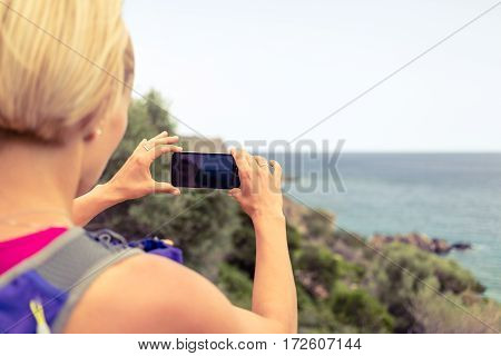 Running woman with backpack looking at inspirational summer coast taking photo with smartphone. Travel and healthy lifestyle outdoors in nature. Female runner or tourist photographing landscape.