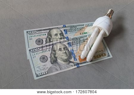 Energy saver tube light bulb with screw in base laying on two 100 dollar bills on grey background, energy saving concept