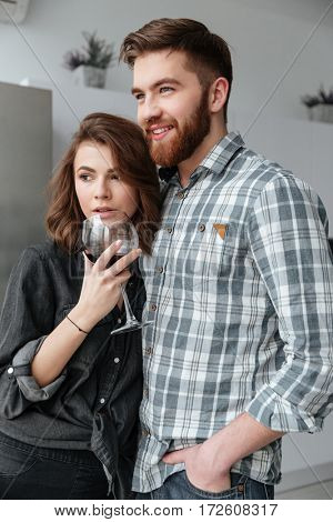 Photo of young loving couple standing in kitchen at home indoors. Drinking alcohol.