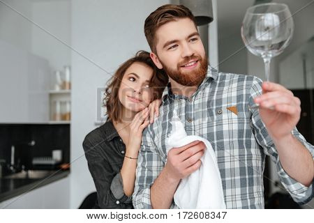 Photo of young cheerful loving couple standing in kitchen at home indoors. Looking at glass.