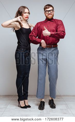 Vertical image of Displeased Woman which showing thumb down and holding hand of Male nerd which showing thumb up