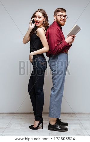 Smiling Woman and Smiling male nerd standing back each other while woman talking on phone and male nerd holding book