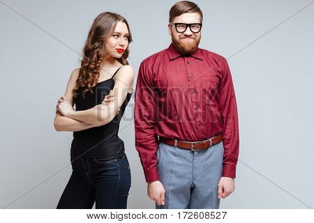 Beauty Displeased woman with smiling male nerd in funny clothes and eyeglasses