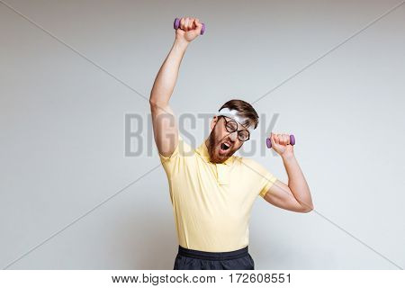 Bearded Male nerd in funny eyeglasses and yellow shirt which training with light dumbbells