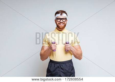 Male nerd in eyeglasses with dumbbells. Isolated gray background