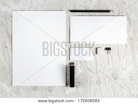 Photo of blank stationery set. Corporate identity template on light wooden background. Mock up for placing your design. Responsive design mockup. Top view.