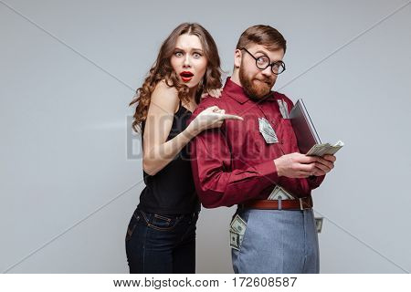 Surprised Girl standing from back of Male nerd which holding money