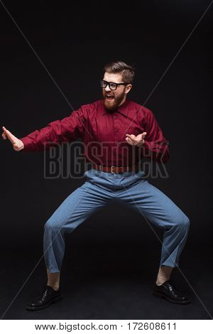 Vertical image of Male fighter nerd posing in studio. Isolated black background