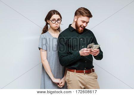 Upset Female nerd in funny eyeglasses standing near the bearded man which recounts the money